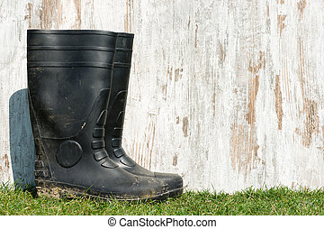 rubber boots on the grass - wheathered wood on a field of ...