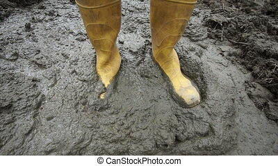 Rubber Boots Stepping Muddy Ground - Close up high angle...
