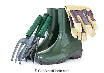 rubber boots with garden tools over a white background