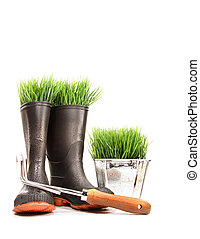 Rubber boots with grass in pot and tool