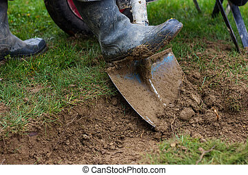 rubber boots with shovel digging out