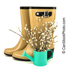 Rubber boots with spring easter flowers pussy willow in the watering can