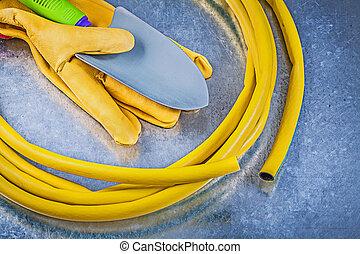 Rubber garden hose protective gloves hand spade on metallic back