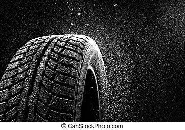 Snow sweeps up a winter tyre cover on a black background