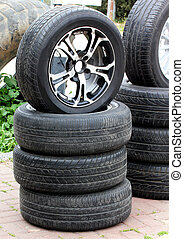 Stack of old dirty rubber tires and wheel