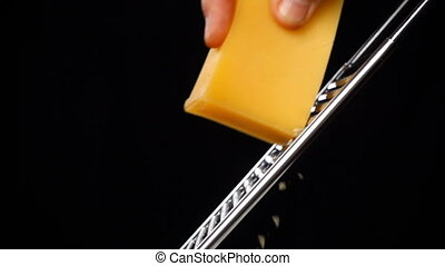 Rubbing the cheese on metal grater isolated on black...