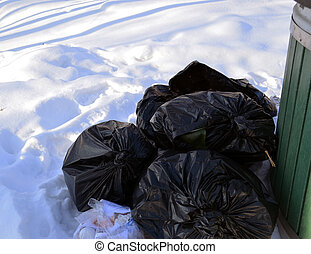 rubbish bags on snow. garbage container in winter