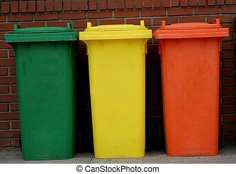 Rubbish bins - Green, yellow and orange rubbish bins in a...