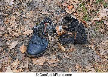 rubbish from two burnt old black shoes on the ground in dry leaves