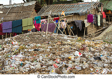 Rubbish in slum area - Laundry drying under a large rubbish...