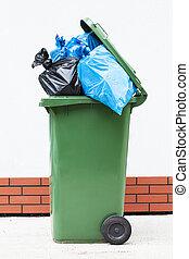 Rubbish sacks in bin - Blue and black rubbish sucks in a...
