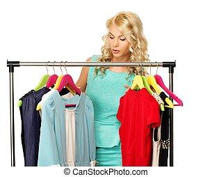 rubio, mujer, escoger, ropa, en, un, estante