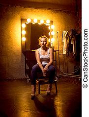 rubio, mujer, posar, en, silla, en, espacio aliño, en, teatro