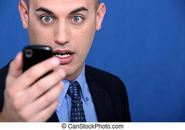 ruchomy, patrząc, telefon, wstrząśnięty, człowiek
