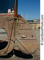An old boat rudder, metal, painted red with rust and dried mud attached to a metal shaft and dangling orange rope.