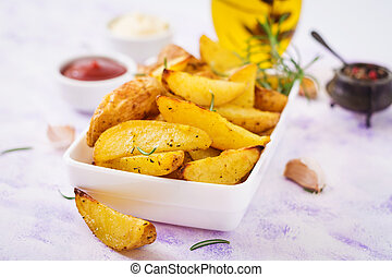 Ruddy Baked potato wedges with rosemary and garlic on a light background