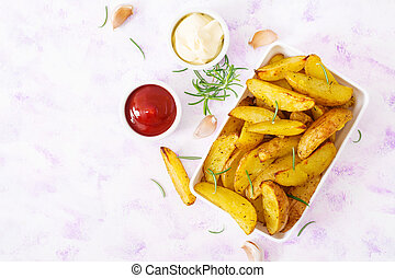 Ruddy Baked potato wedges with rosemary and garlic on a light background. Top view. Flat lay