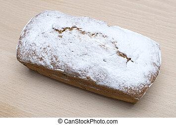 Ruddy rectangular cake on a wooden board