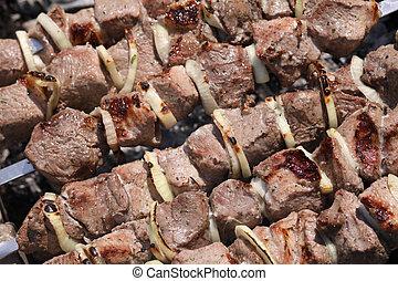 The ruddy shish kebab is fried on coals