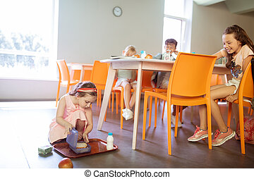 Rude children laughing at the girl dropping her tray with food