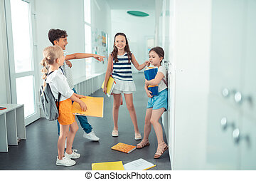 Rude children throwing papers of girl on the floor while bullying her