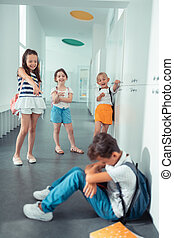 Rude violent girls laughing at dark-haired boy at school