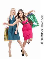 Rude women. Young blond hair women stretching out her leg and another one brown hair falling while isolated on white