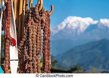 Rudraksha rosaries hanging on wooden hook in fronh of white...