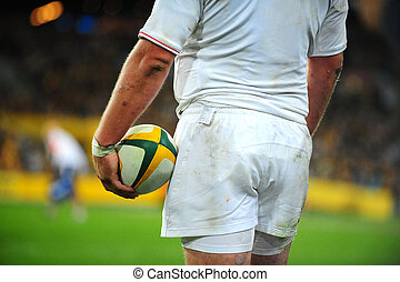 Rugby - A rugby player holds the ball as he stares across...
