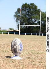 Rugby ball positioned on a grass pitch with the goal in the background