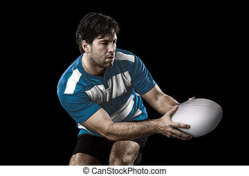 Rugby player in a blue uniform. black Background.