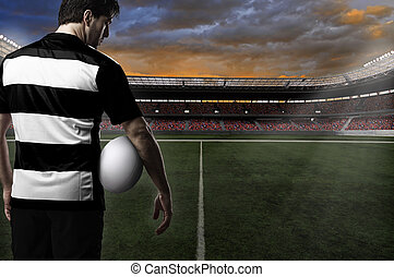 Rugby player in a black and white uniform on a stadium.