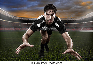 Rugby player in a black and white uniform giving a tackle on...