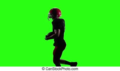 Rugby player running in a red helmet with the ball in his hands. Slow motion