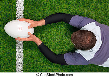 Overhead photo of a rugby player diving over the line to score a try with both hands holding the ball.