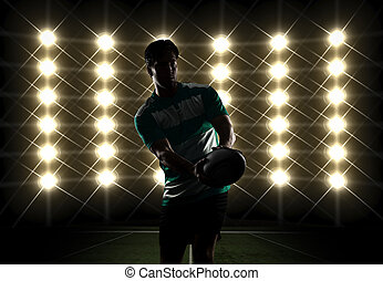 Rugby player silhouette in front of lights in a green...