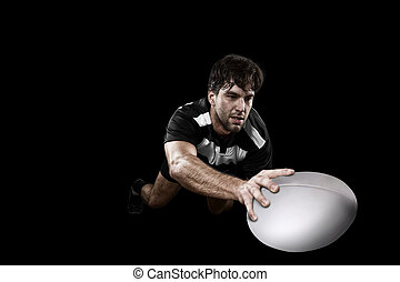 Rugby player in a black and white uniform. Black Background