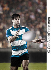 Rugby player in a blue uniform on a stadium.