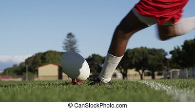 Rugby player throwing the rugby ball - Side view low section...