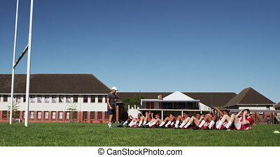 Side view of a teenage multi-ethnic male team of rugby players wearing red and white team strip, training on the playing field, doing sit ups in a row, with a coach next to them in slow motion