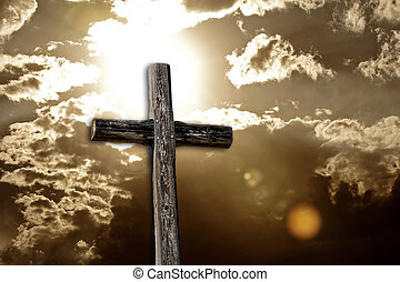 Christian image of a rugged cross highlighted against a sepia-toned bright sun and cloudy sky - intentional lens flare for dramatic effect.