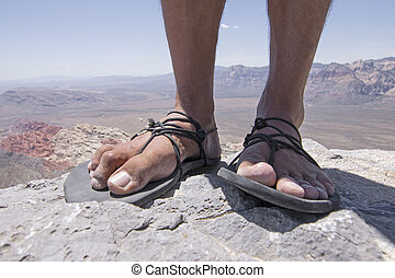 Rugged feet in primitive sandals on mountain - Closeup of...