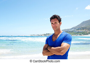Rugged good looking man standing at the beach