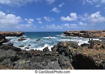 Rugged Lava Rocks Surrounding the Cove of Aruba's Black Sand Beach