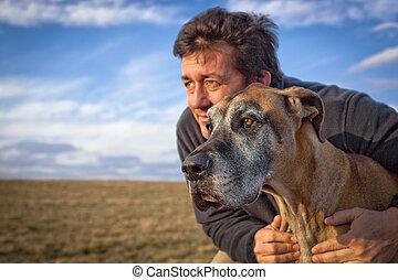 Rugged man hugging great Dane