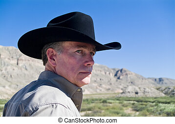 A portrait man in a black western style hat with cliffs and a bright blue sky in the background.