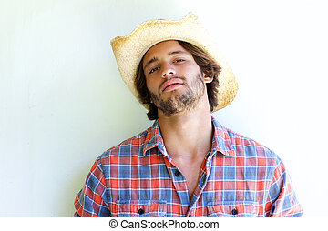 Rugged young man wearing cowboy hat - Close up portrait of...