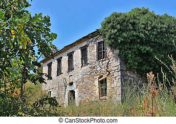 Ruin of an old, abandoned stone house among trees and high grass, at south Pelion, Greece