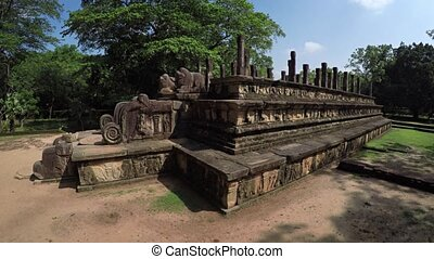 Ancient stone ruins of King Nissankamalla's council chamber, with intricate relief carvings, in Polonnaruwa, Sri Lanka, an important historical capital.
