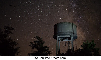 Ruined concrete water tank night time lapse with moving stars